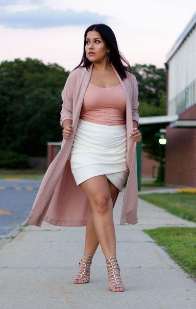 Joven de talla grande modelando una falda ajustada con top rosa y cardigan largo