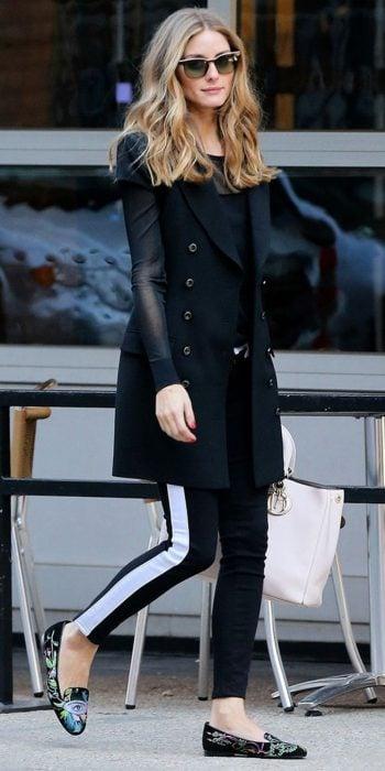Chica caminando por la calle, con leggins negros con detalle blanco a los lados, blusa negra y zaco negro, con bolsa beige en mano