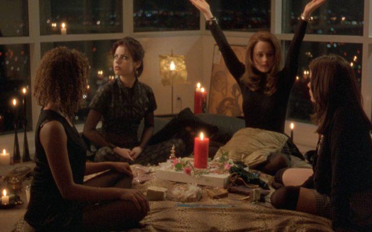 Cuatro chicas en una habitación, durante una pijamada con velas rojas encendidas, sentadas en el piso rodeadas de almohadas, escena película Jóvenes Brujas