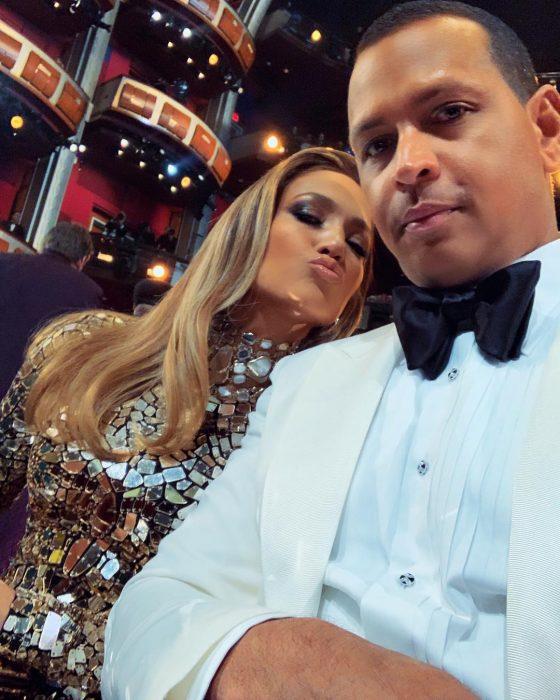 Pareja vestida con atuendos de gala, Jennifer López