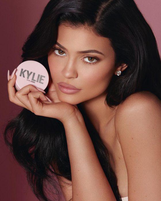 Kylie jenner sosteniendo un polvo translucido de su línea de maquilaje