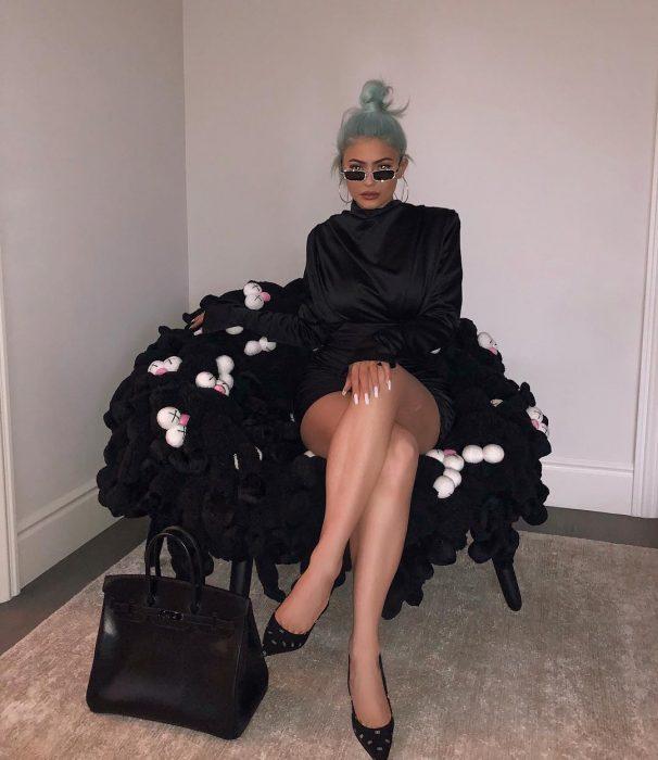 Kylie Jenner sentada en un sofá usando un vestido negro