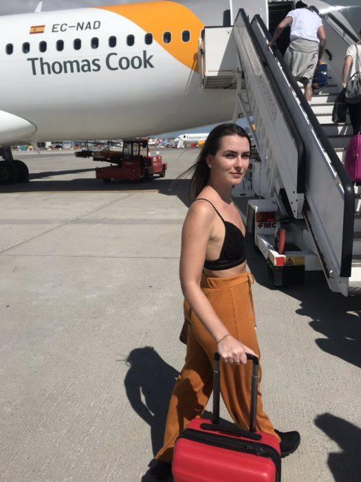 chica llevando su maleta para subir al avión