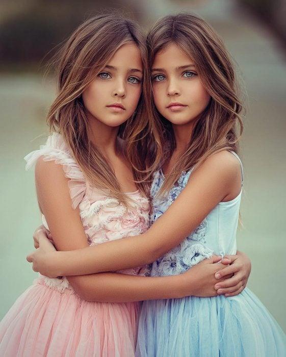 Gemelas Ava Marie y Leah Rose Clements en sesión fotográfica con vestidos rosa y azul