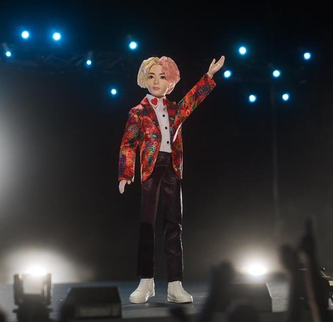 Muñeco inspirado en el cantante de la banda de K-pop, BTS, V, usando un saco de color rojo con pantalones de color café, tenis y camisa blanca
