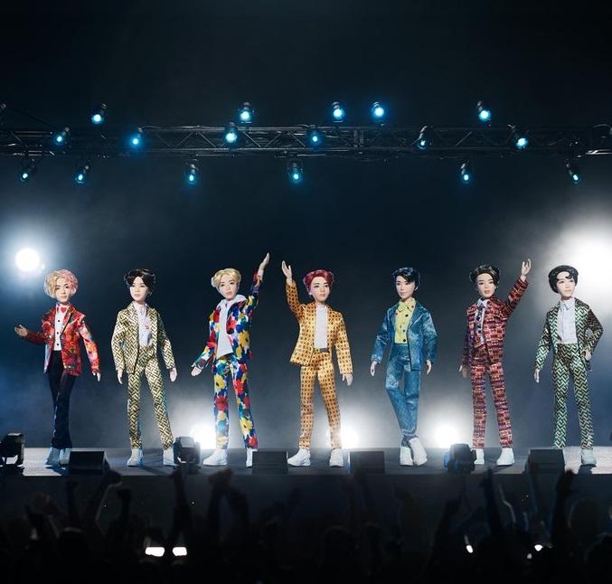 Muñecos de Mattel inspirados en el grupo musical coreano de k-Pop BTS parados en un escenario en negros y con luces azules