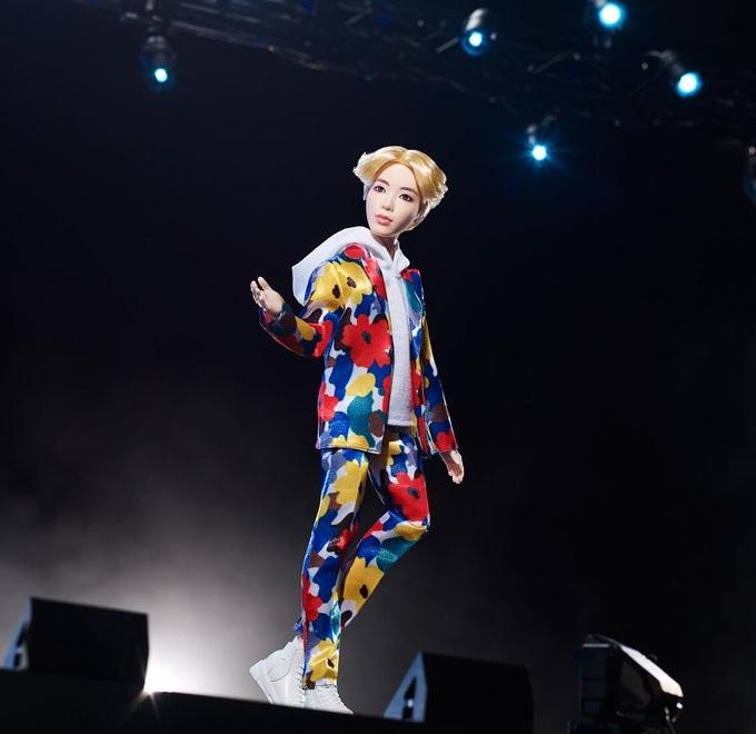 Muñeco inspirado en el cantante de la banda de K-pop, BTS, Jin, usando un traje con estampado floral tenis y sudadera blanca