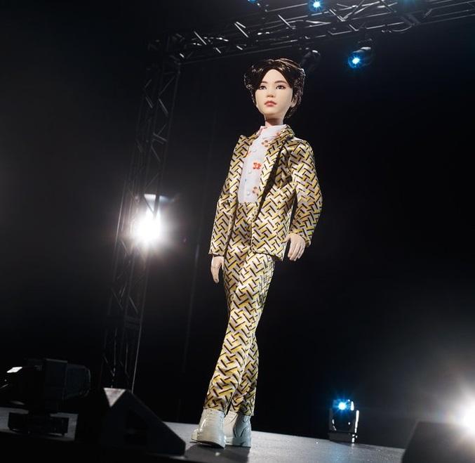 Muñeco inspirado en el cantante de la banda de K-pop, BTS, Suga, usando un traje de lineas en color amarillo con café, tenis y camisa blancas