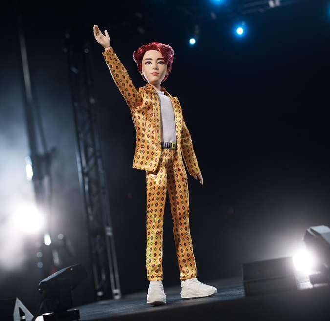 Muñeco inspirado en el cantante de la banda de K-pop, BTS, Jungkook, usando un traje amarillo con puntos de colores rojos y verdes, tenis y camisa blanca