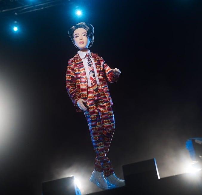 Muñeco inspirado en el cantante de la banda de K-pop, BTS, Jimin, usando un traje de estampado en color rojo, corbata, tenis y camisa blanca