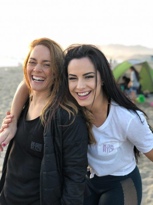 Madre de cabello rubio e hija de cabello castaño en la playa sonriendo mientras se abrazan