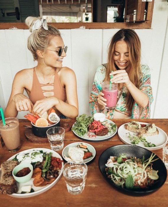 Mejores amigas sonriendo y comiendo en restaurante
