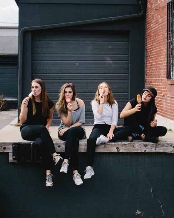 Grupo de mejores amigas sentadas en la calle comiendo una paleta helada