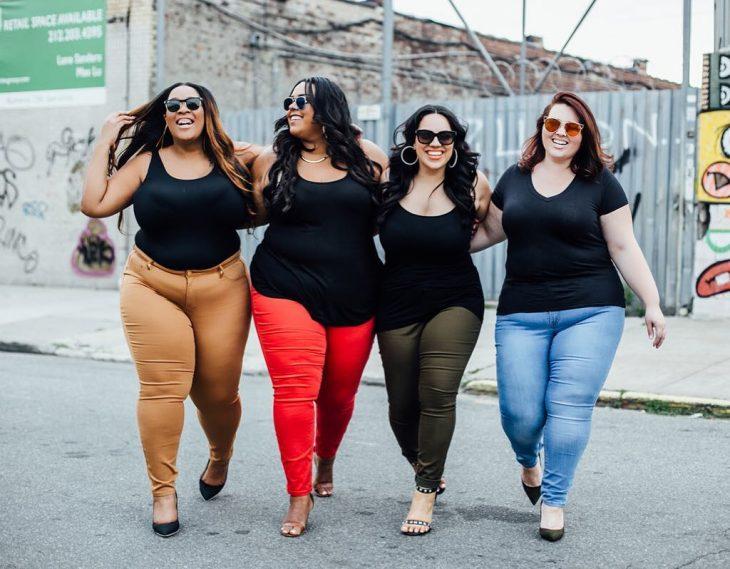 Mejores amigas caminan por la calle abrazadas y sonriendo, mujeres con sobrepeso felices