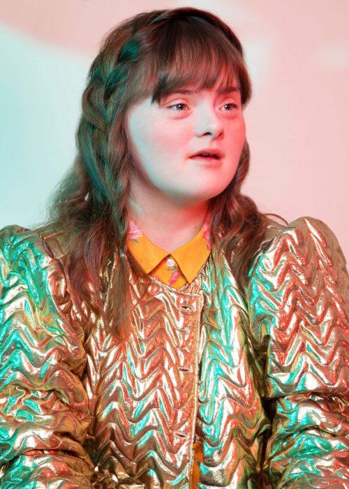 Modelo con síndrome de Down usando chaqueta en metálica, blusa amarilla, con cabello tranzado, mirando de perfil