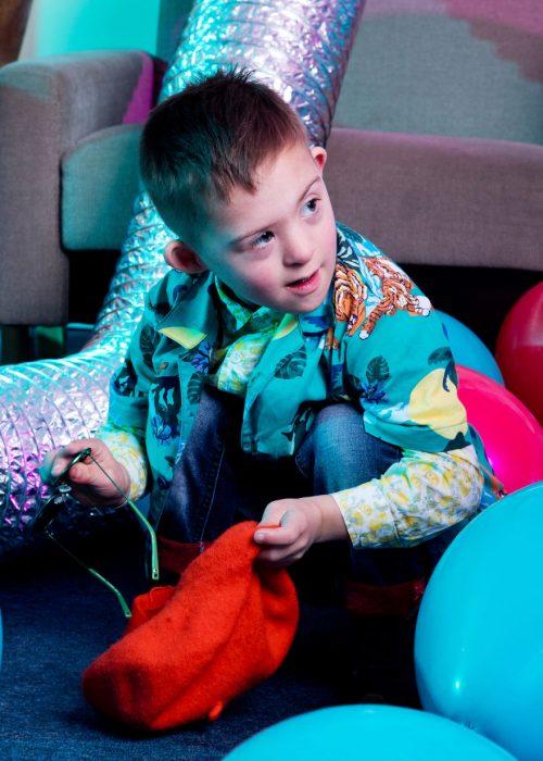 Niño modelo con síndrome de Down guardando unas gafas oscuras en un saco de tela rojo en una sala llena de globos