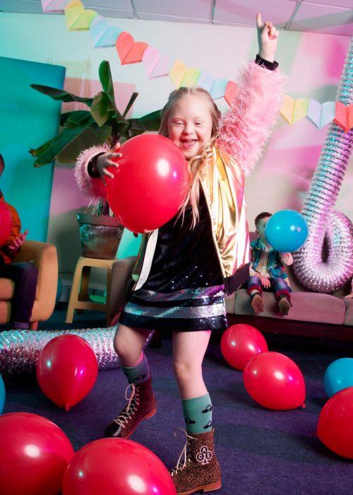 niña modelo con síndrome de Down jugando en una sala de espera con globos rojos, zalzando su mano izquierda para señalar el techo y sosteniendo un globo con su mano derecha