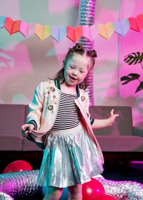 niña modelo con síndrome de Down bailando en una sala de espera llena de globos rojos y decorada con corazones de papel de colores