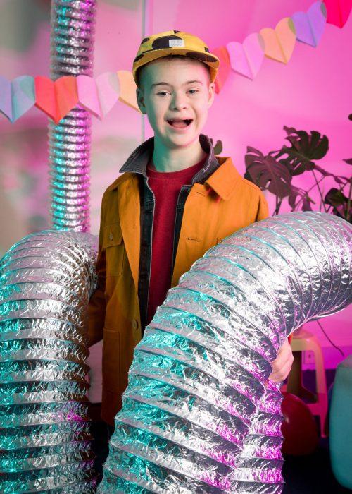 niño modelo co síndrome de Down sosteniendo un par de tubos metálicos ligeros, sonriendo, usando chaqueta y gorra amarillas