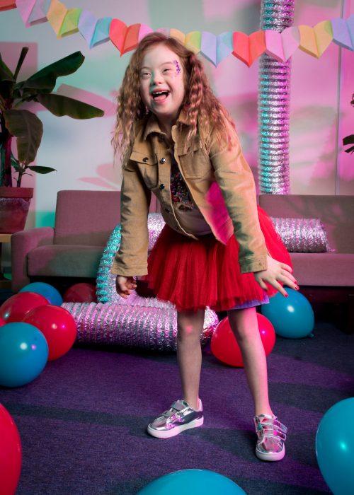 niña con síndrome Down modelando falda de tutu en color rojo, usando tenis y chqueta café de pana, sonriendo, dentro de una sala de espera decorada con globos en azul y rojo