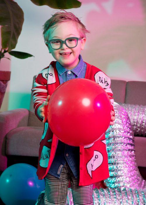 niño modelo con síndrome de Down sosteniendo un globo rojo entre sus manos, llevando gafas de marco gris, suéter rojo, camisa denim. pantalón a cuadros
