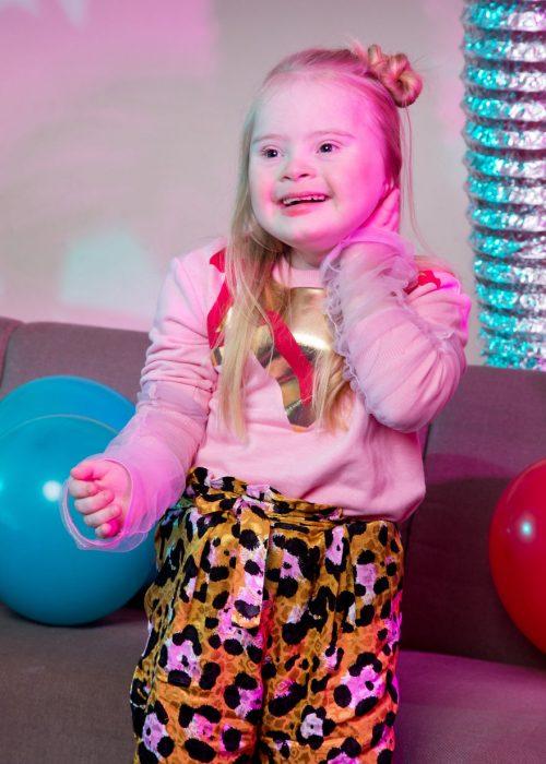 niña modelo con síndrome de Down acariciando su cabello rubio, sonriendo de manera nerviosa, llevando pantalón flojo con decorado en manchas y sudadera rosa, parada frente a un sofá con globos rojos y azul