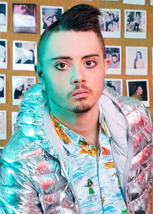 Modelo con síndrome de Down usando chaqueta metálica, camisa hawaiana, con ojos delineados, modelando dentro de una oficina decorada con fotografías antiguas