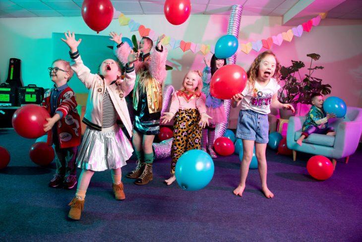 Niños con síndrome de Down jugando con globos de color azul y rojo dentro de una sala de espera