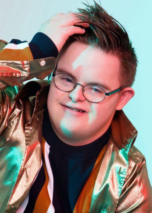 Modelo con síndrome Down usando anteojos, chaqueta metálica, acariciando su cabello ligeramente con la mano izquierda y sonriendo para una fotografía