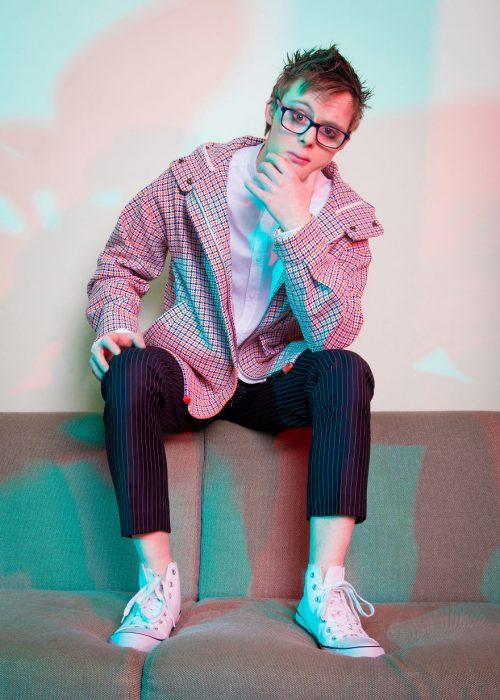 Modelo con síndrome de Down sentado sobre un sofá café, acariciando su barbilla con su mano izquierda y mirando fijamente al frente