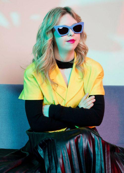 Modelo con síndrome de Down sentada en un sofá, llevando falda de cuero en negro, con brazos cruzados, usando gafas de sol grandes con marco morado