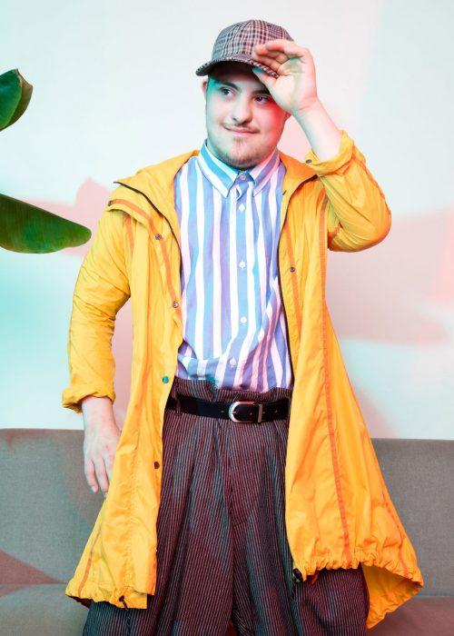 Modelo con síndrome de Down sosteniendo su gorra por la parte de frente, de pie frente a un sofá, modelando un pantalón de satin a cuadros amplia, camisa a rayas y gabardina amarilla