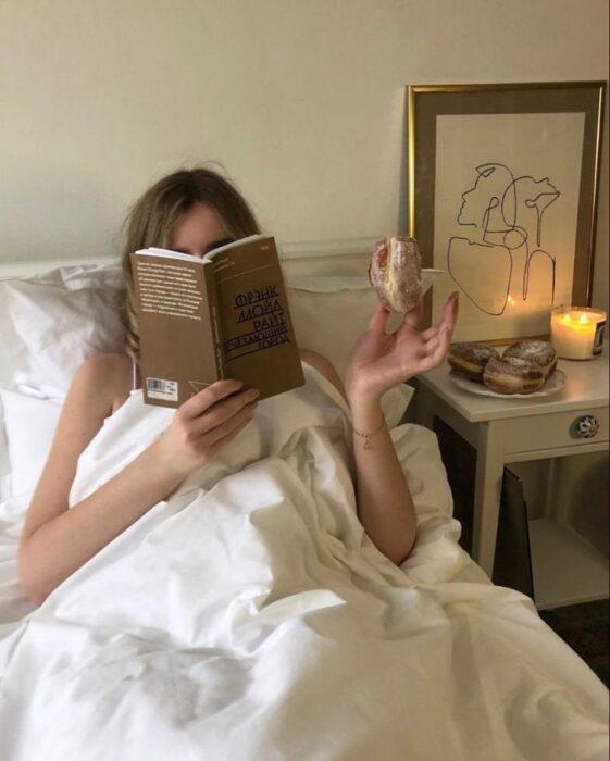 Mujer leyendo en la cama y comiendo dona