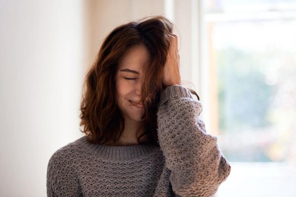 Chica con cabello castaño y suéter gris sonriendo