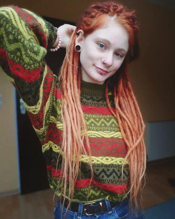 Chica pelirroja con rastas y suéter