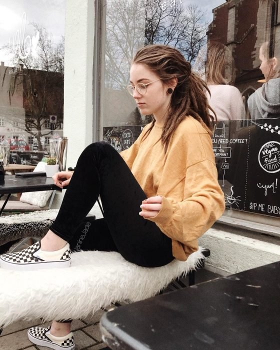 Chica con rastas sentada en un café
