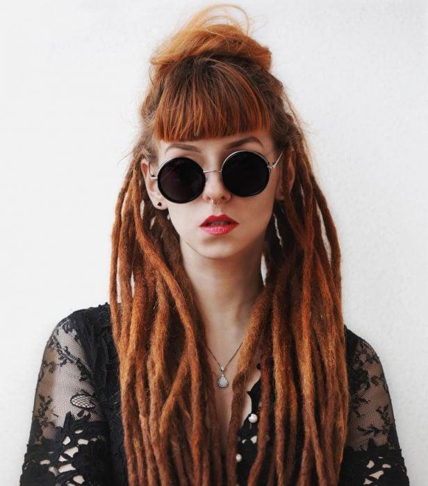 Chica pelirroja con rastas y lentes redondos de sol