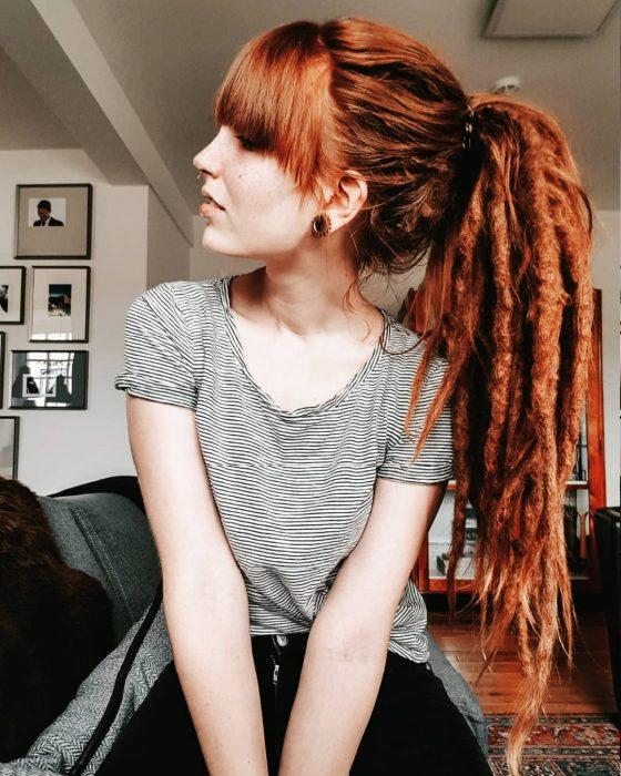 Chica pelirroja con rastas y una coleta de caballo