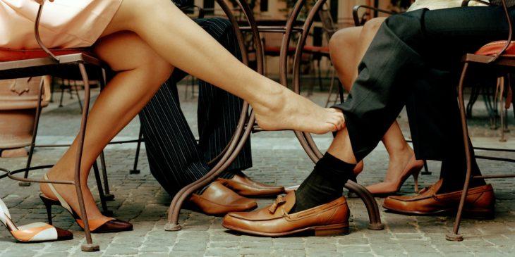 Grupo de personas reunidas alrededor de una mesa, pie de una chica descalzo acariciado la pierna de un hombre con traje sastre.
