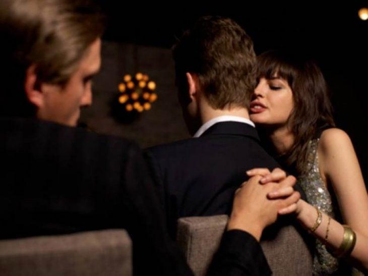 Dos hombres y una mujer sentados en su sofá, mujer recargada en el cuello de un hombre sosteniendo pa sus espaldas la mano de un segundo hombre