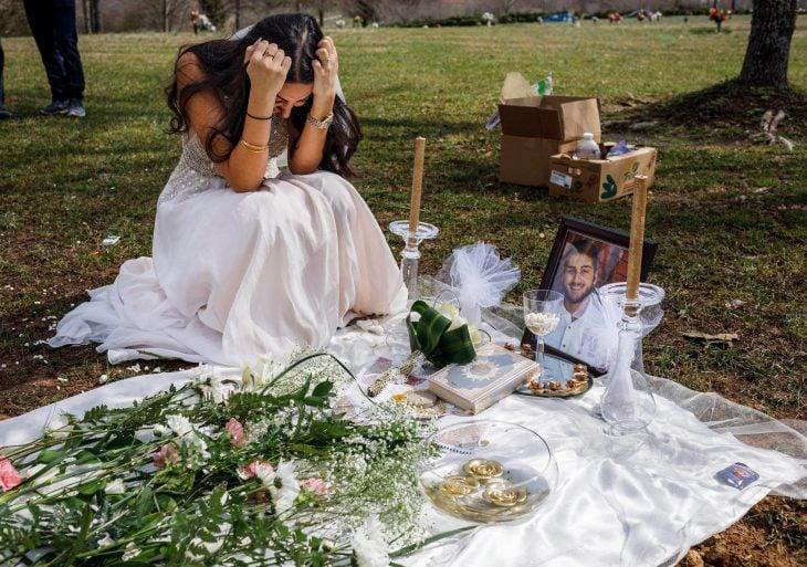 Mujer con su vestido de novia llorando en la tumba de su prometido