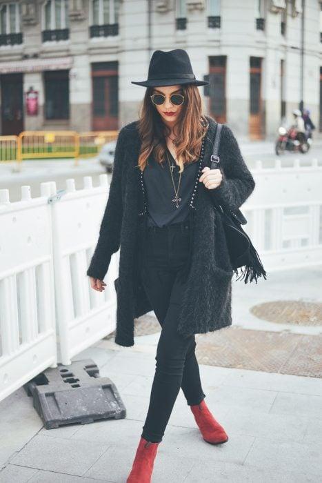 Chica caminando por la ciudad con atuendo y sombrero negro y botines rojos