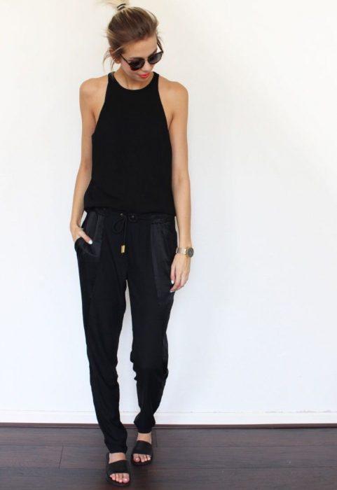 Chica reposando en pared con blusa sin mangas, pantalón ancho negro y sandalias
