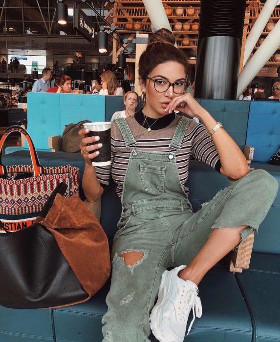 Chica con overol de mezclilla verde y camisa a rayas tomando un café