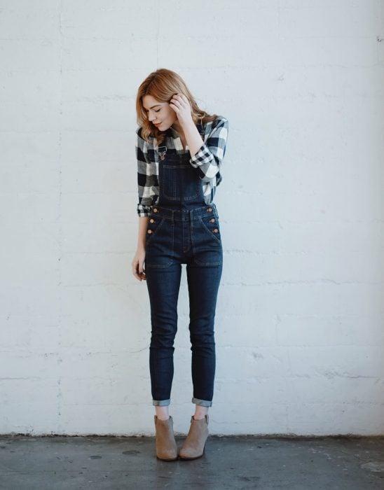 Chica con overol de mezclilla y camisa de cuadros