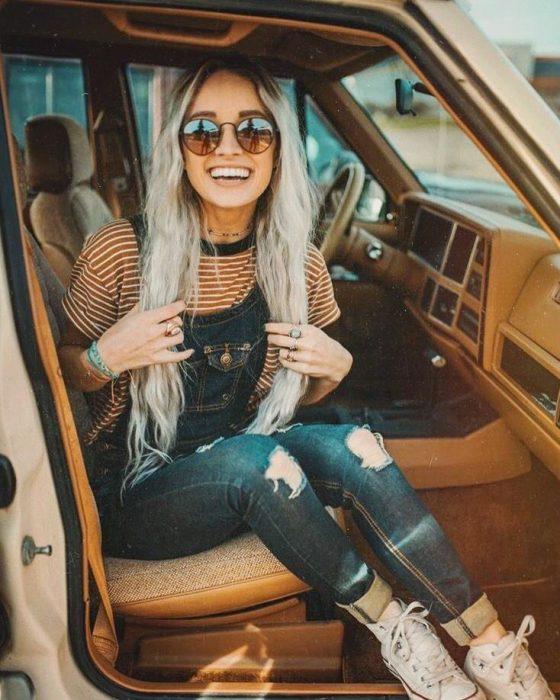 Chica con overol de mezclilla y camisa a rayas con lentes de sol