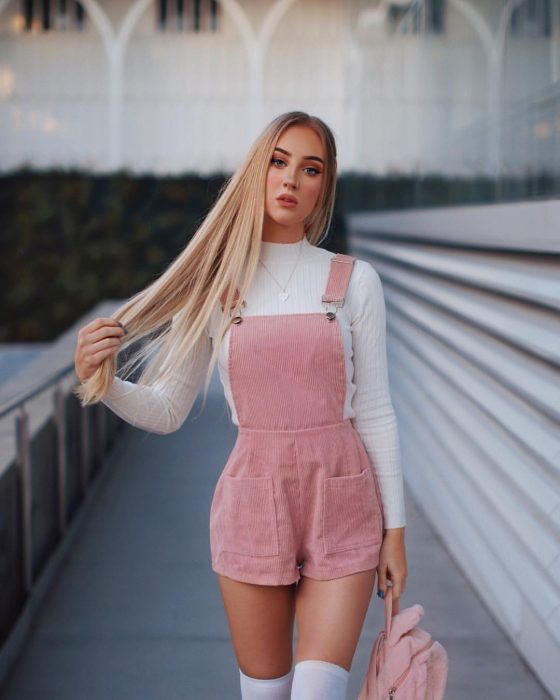 Chica rubia con overol de pana rosa y mochila rosa