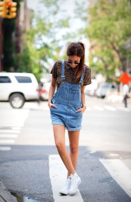 Chica con tenis blancos, overol corto, camisa de animal print en la calle