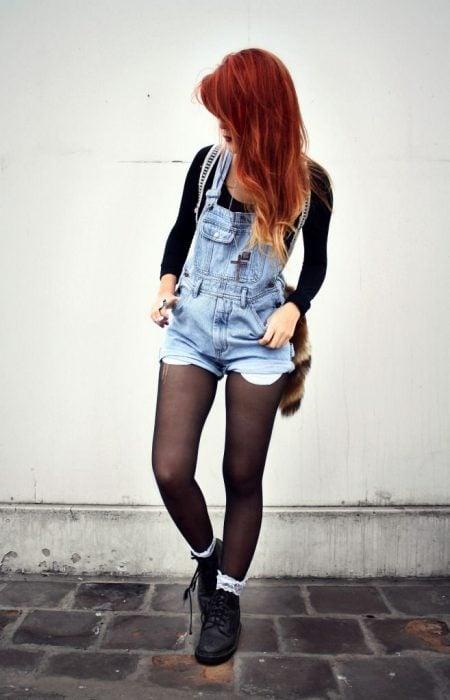 Chica de cabello rojo con overol de mezclilla y medias