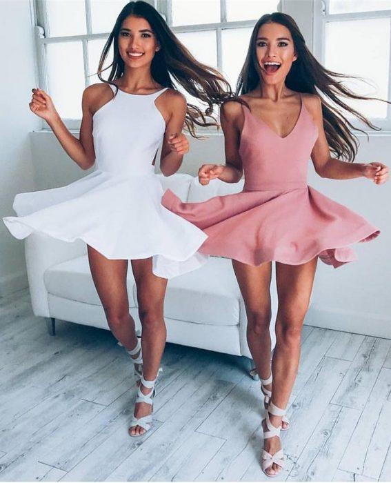 Gemelas de cabello castaño con vestidos que combinan, blanco y rosa